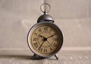 Old fashioned alarm clock on a white table against a white wall