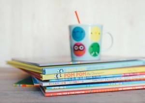 A pile of story books with a mug on top of them