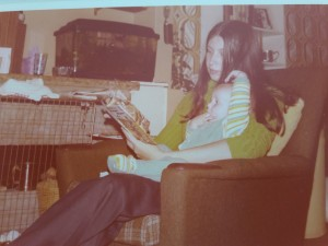 Sarah as a baby, sitting on a sofa with her Mum reading a book to her