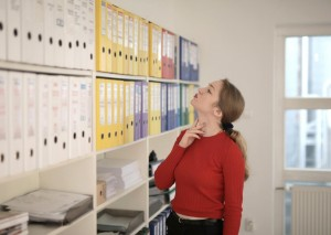 A woman selecting from a number of files on a shelf