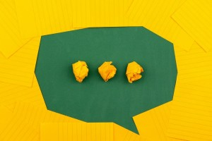 Yellow background and green speech bubble with 3 yellow dots in the middle
