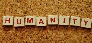 Scrabble tiles spelling out the word humanity on a cork board