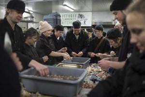 Group of volunteers preparing vegetables in a large kitchen