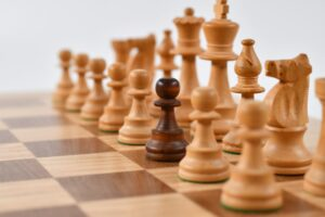 A set of white chess pieces with one black piece to indicate what it is like to live our own truth